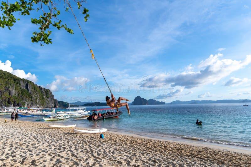 A woman on a swing at the 7 commandos island beach in a El nido, Palawan, Philippines Nov 18,2018 A. Nov 18,2018 A woman on a swing at the 7 commandos island stock images