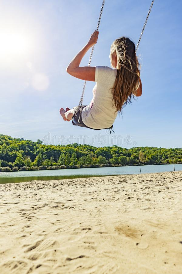 Woman on a swing at a lake stock photography