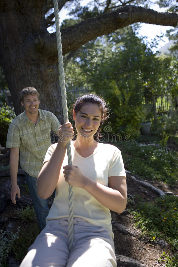 Woman swinging on garden rope swing, man pushing her in background, smiling, front view, portrait royalty free stock photography