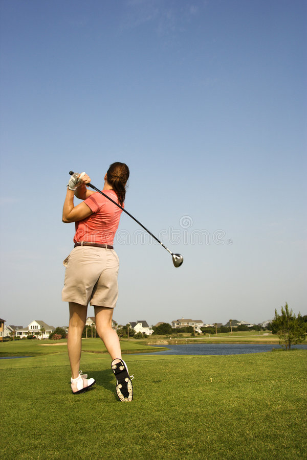 Woman swinging golf club. stock images