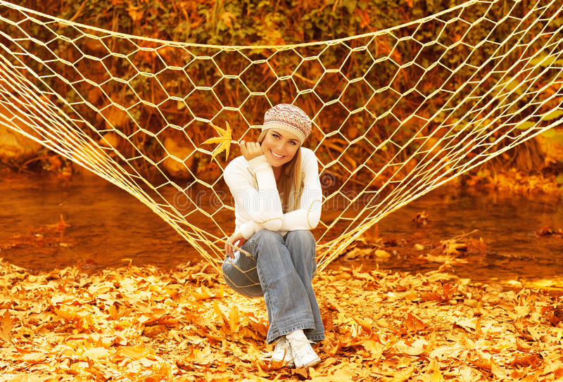 Woman swinging in hammock. Picture of attractive woman swinging in hammock on backyard, happy girl holding dry orange leaf in hand, cute female having fun in stock photo