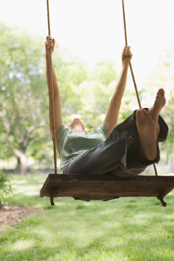 Woman Swinging on Swing. A young woman is swinging on a swing in a park setting. Vertical shot royalty free stock photography