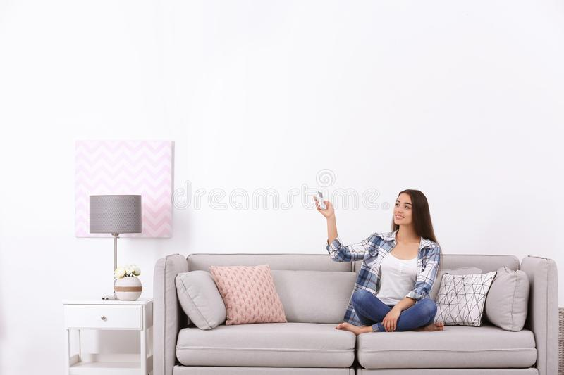 Woman switching on air conditioner while sitting on sofa near white wall. Young woman switching on air conditioner while sitting on sofa near white wall stock images