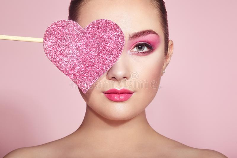 Woman with symbol Valentines day. Beauty Young Fashion model Girl with Symbol Valentine Heart shaped in hand. Love. Beautiful young Woman with Holiday Makeup stock photography