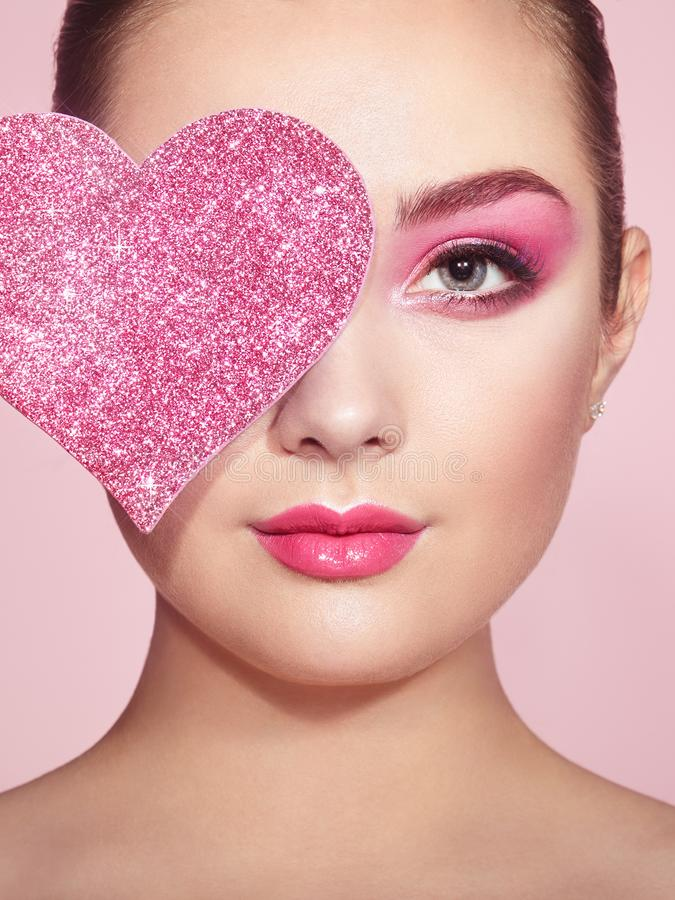 Woman with symbol Valentines day. Beauty Young Fashion model Girl with Symbol Valentine Heart shaped in hand. Love. Beautiful young Woman with Holiday Makeup royalty free stock image