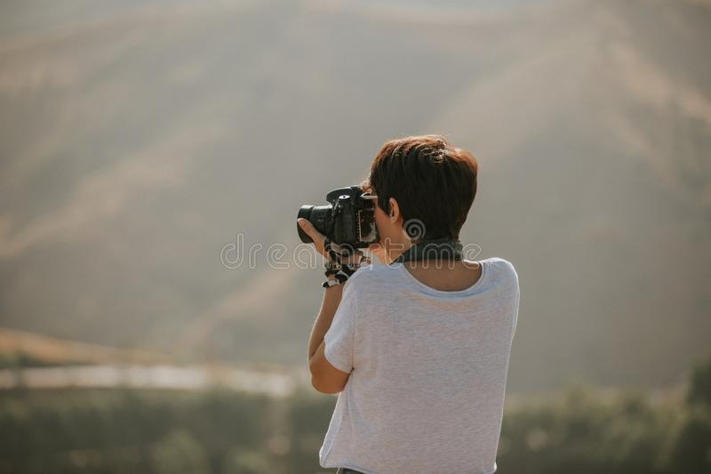 Woman in t-shirt taking a photo with a dslr camera in nature with daylight. stock photos