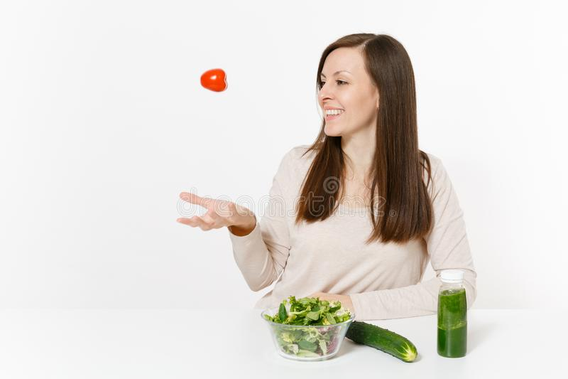 Woman at table with green detox smoothies, fresh salad in glass bowl, tomato, cucumber isolated on white background. Proper nutrition, vegetarian food, healthy royalty free stock photography