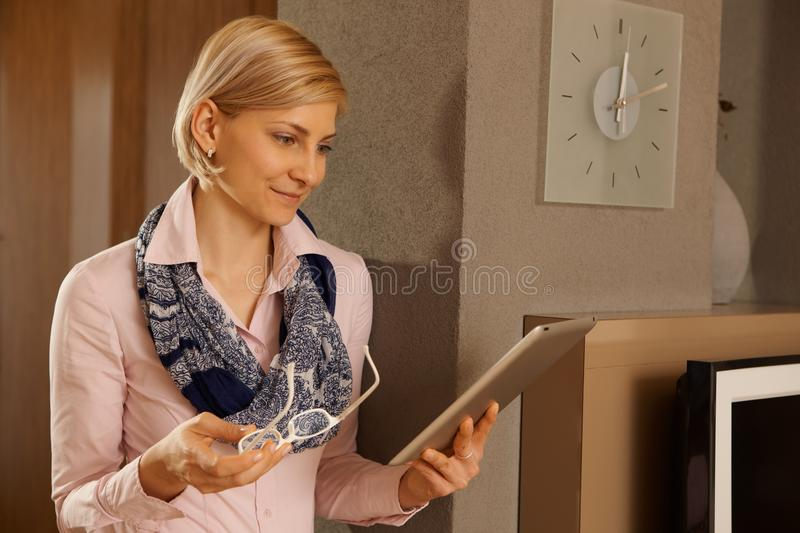 Woman with tablet. Blonde woman holding tablet, reading at home stock image