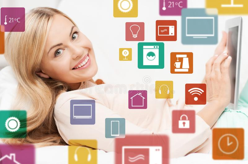 Woman with tablet computer and smart home icons royalty free stock image