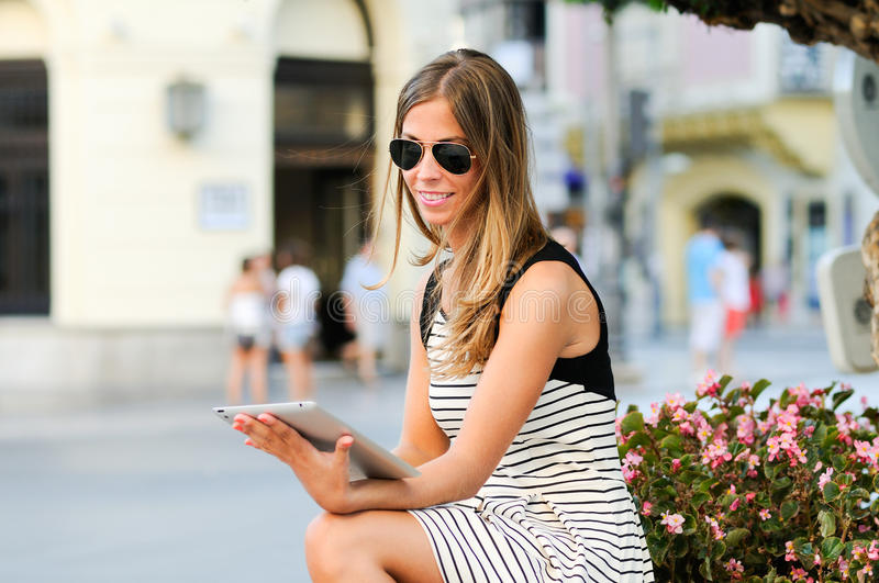 Woman with tablet computer in urban background