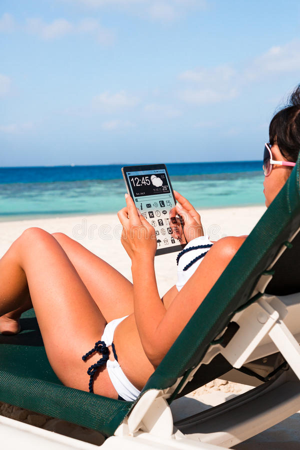 Woman with a tablet in hands. Woman on vacation lies in a sun lounger on the beach with a tablet in hands copy space display stock photography