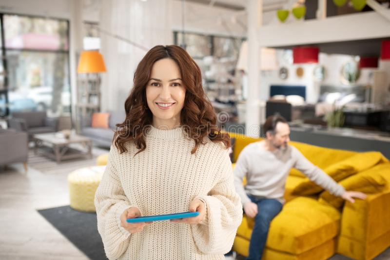 Woman with tablet in her hands smiling nicely royalty free stock image