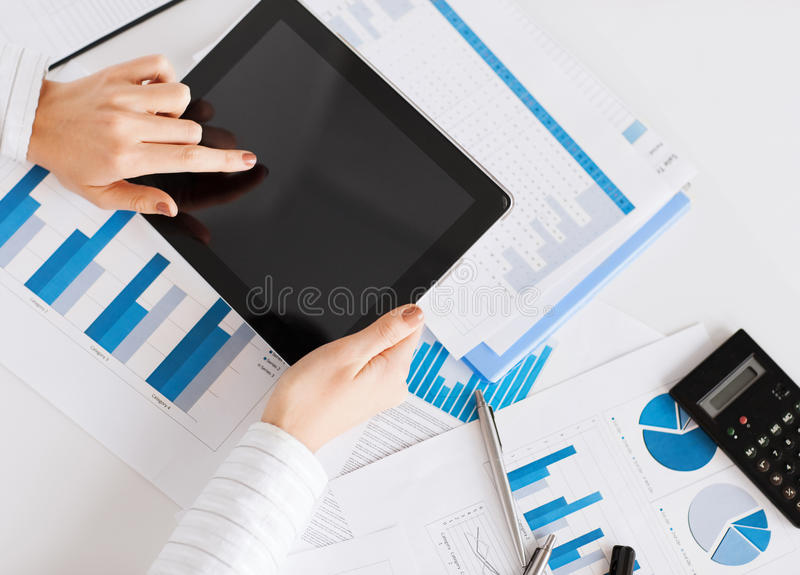 Woman With Tablet Pc And Chart Papers Stock Photography