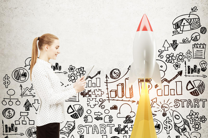 Woman with a tablet, startup rocket. Side view of a blonde businesswoman with a laptop standing near a concrete wall with a rocket and start up icons. Mock up stock photography