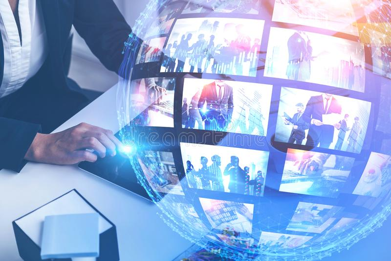 Woman with tablet, streaming interface. Woman using tablet on office table with double exposure of futuristic video streaming interface. Concept of hi tech and stock image