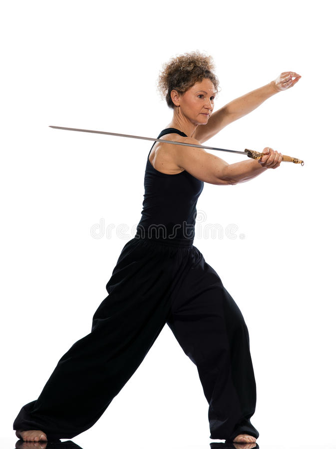Woman tai chi. Mature woman praticing tai chi chuan with sword in studio on isolated white background royalty free stock image