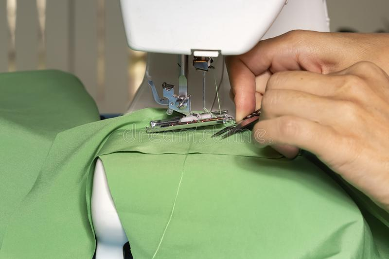 Woman tailor sews fabric on a sewing machine in the workshop. Close-up. Copy space royalty free stock images