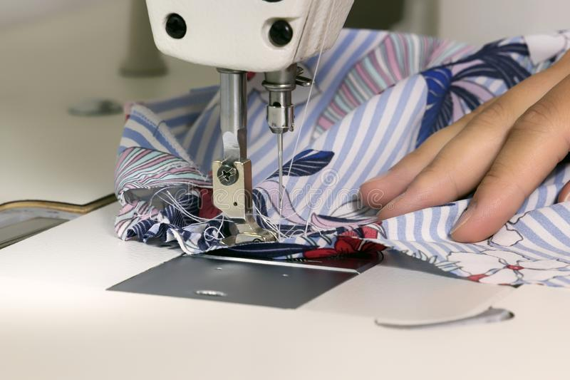 Woman tailor sews fabric on a sewing machine in the workshop. Close-up. Copy space stock photo