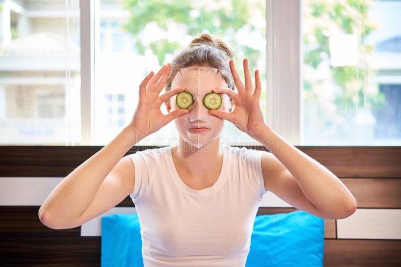 Woman take care of her face. Portrait of young woman applying facial mask on her face and holding slices of cucumbers in front of her eyes sitting in bedroom royalty free stock photo