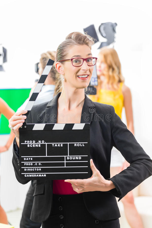 Woman with take clap at video production on film set. Woman with take clap or board on Film Set of video production for TV, television, news or commercial stock photo