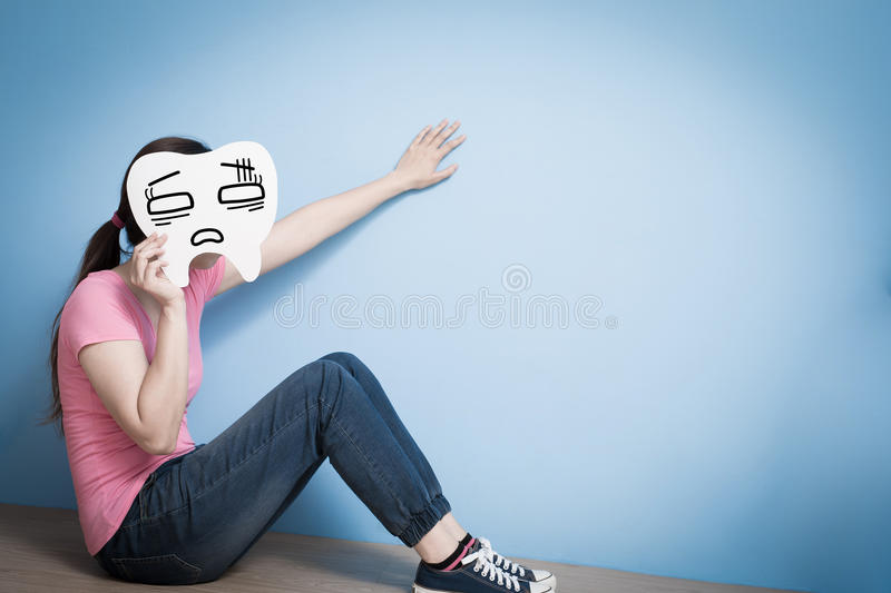 Woman take confuse tooth. On blue background royalty free stock photos