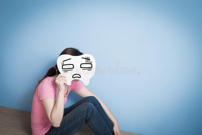 Woman take confuse tooth. On blue background stock images