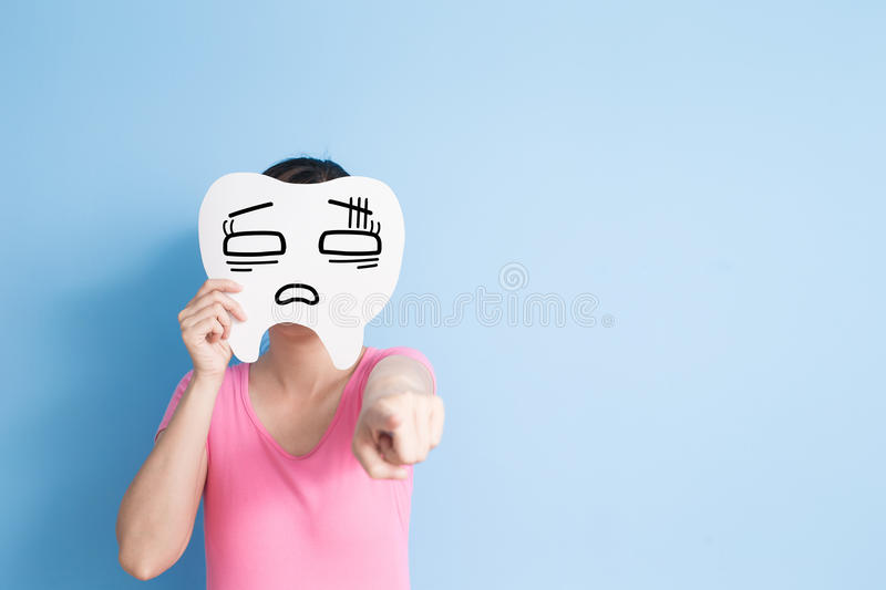 Woman take confuse tooth. And show something on the blue background royalty free stock photos