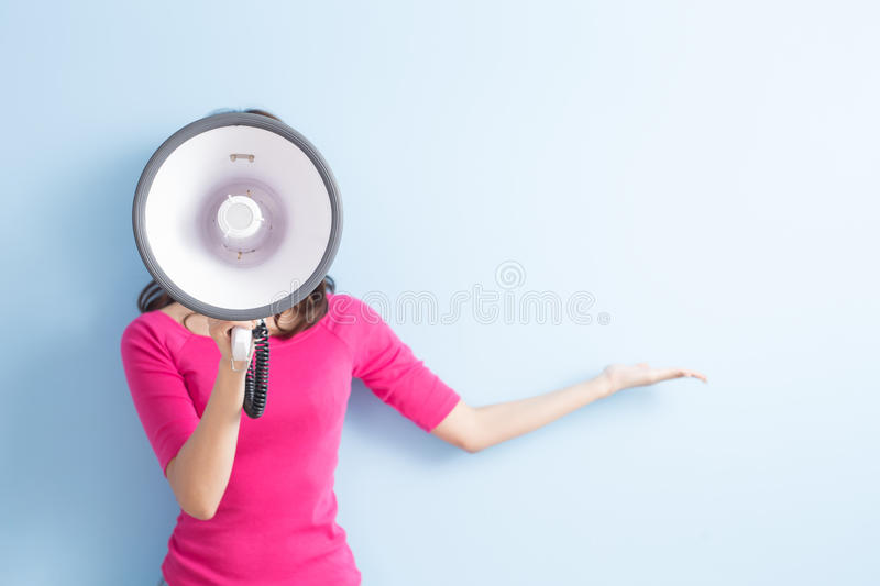 Woman take microphone. And show something to you on blue background royalty free stock images