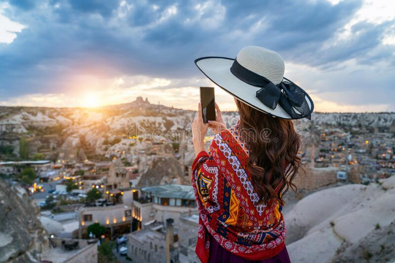 Woman take a photo with her smartphone at Goreme, Cappadocia in Turkey. royalty free stock image