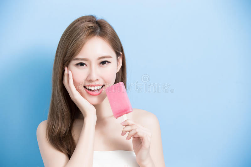 Woman take popsicle. And touch her face on the blue background royalty free stock photography