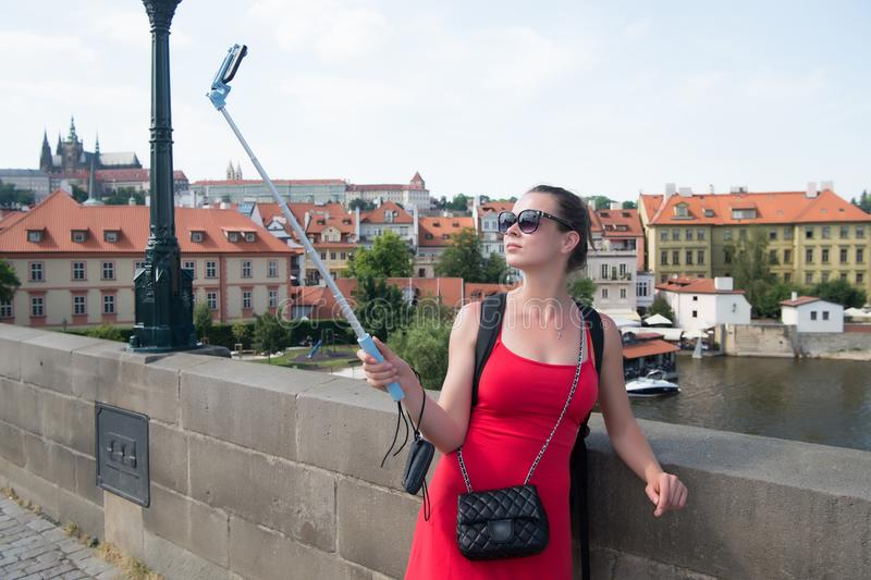 Woman take selfie with mobile phone in prague, czech republic. Woman with smartphone on stick at bridge over river. Girl tourist w. Ith fashion look and sensual stock photography