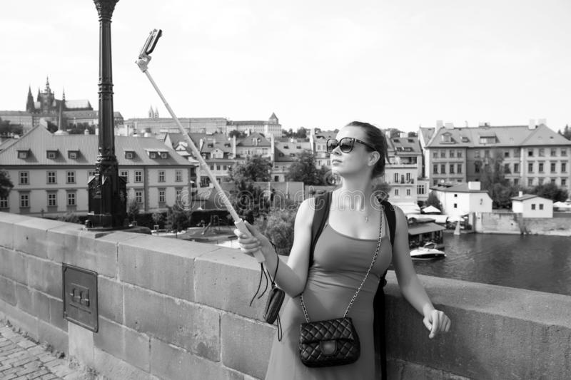 Woman take selfie with mobile phone in prague, czech republic. Woman with smartphone on stick at bridge over river. Girl. Tourist with fashion look and sensual royalty free stock images