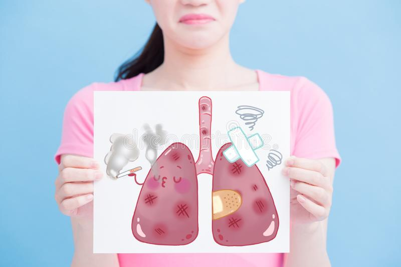 Woman take unhealth lung billboard. On the blue background royalty free stock photo
