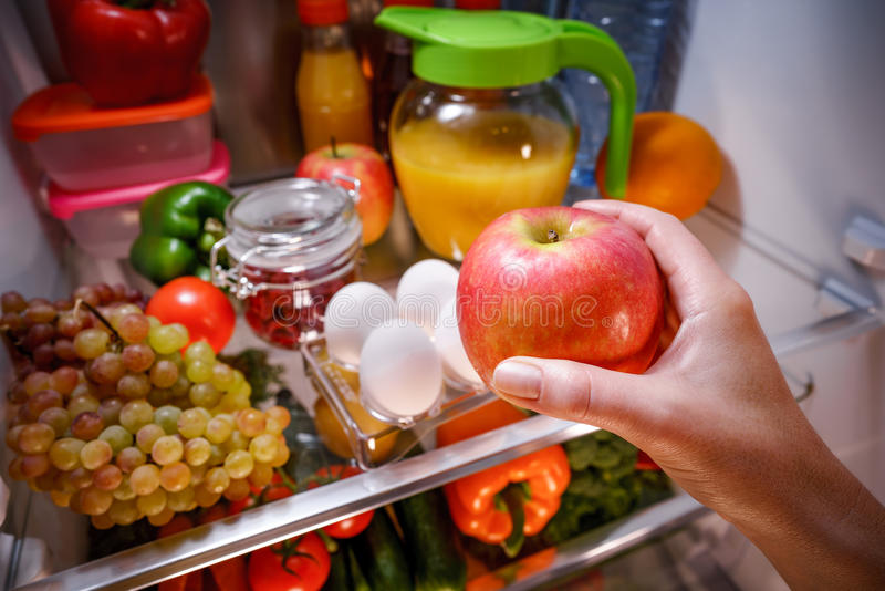 Woman takes the apple from the open refrigerator. stock images