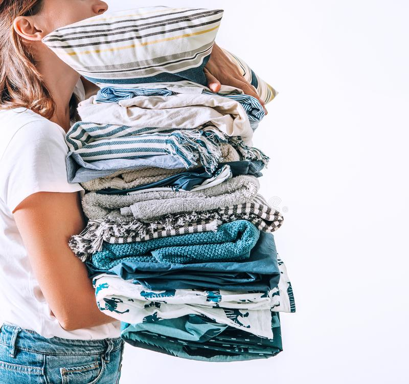 Woman takes in hands big pile blue and beige blankets, towels and other home textile stock image