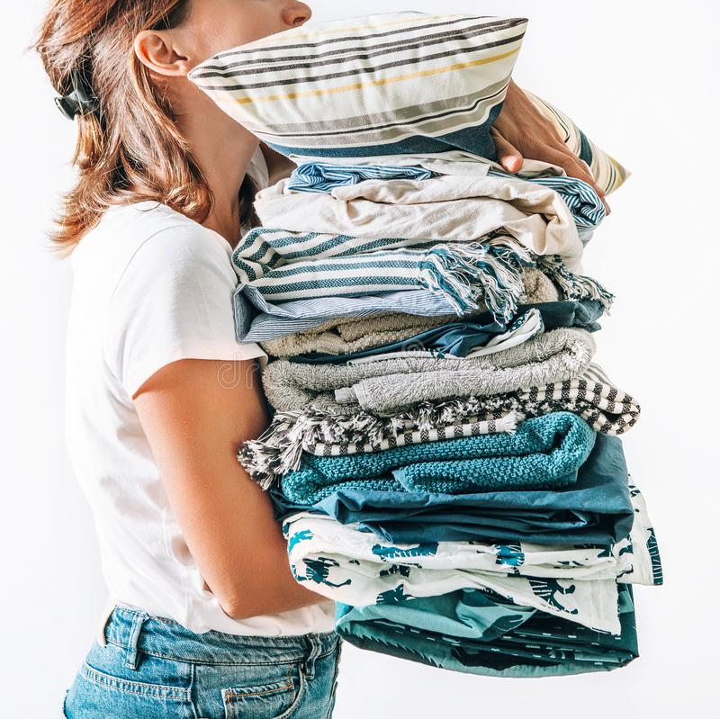 Woman takes in hands big pile blue and beige blankets, towels and other home textile royalty free stock photos