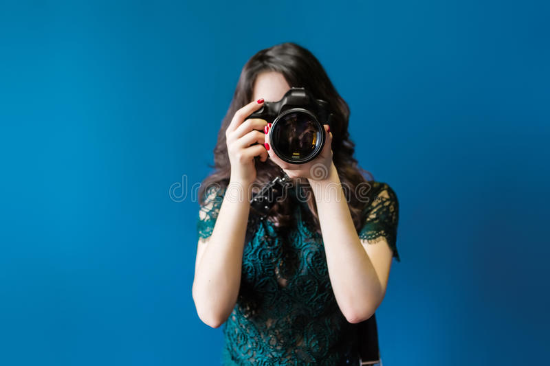 Woman takes images holding photographic camera. On a dark blue royalty free stock image