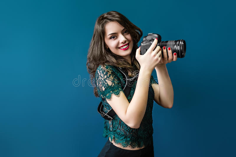 Woman takes images holding photographic camera. On a dark blue stock image