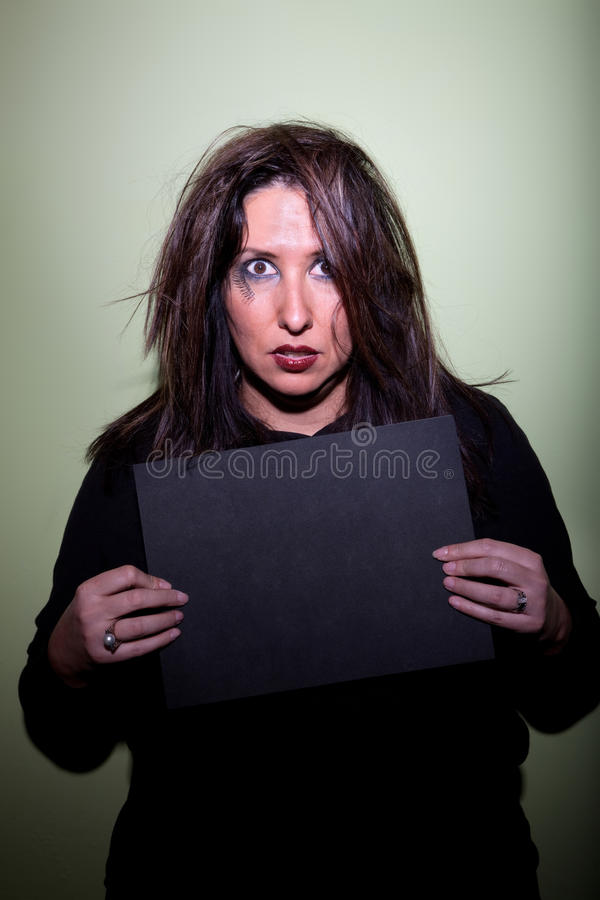 Woman takes mugshot. Deranged looking woman in mugshot with blank board royalty free stock images