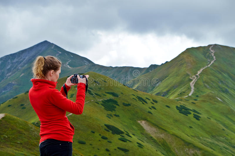 Woman takes a photo on a mountain trail. Woman in red jacket with a camera takes a photo on a mountain trail in Tatra National Park royalty free stock photo
