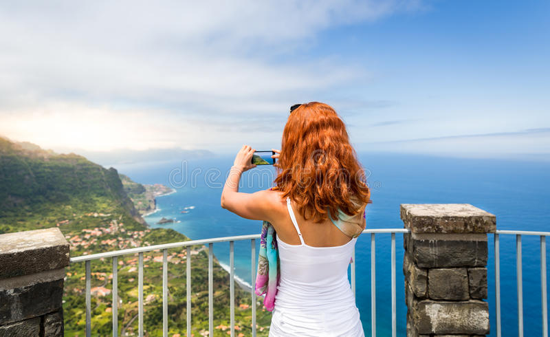 Woman takes photo of seaside landscape royalty free stock photography