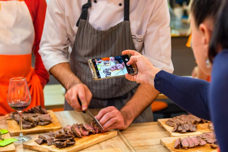 Woman takes picture of chef slicing steak stock images