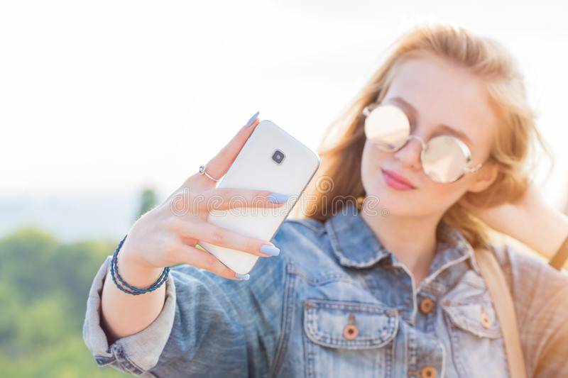 A woman takes a selfie on the background of nature. Smartphone in focus. A woman in sunglasses takes a selfie on the background of nature. Smartphone in focus stock photography