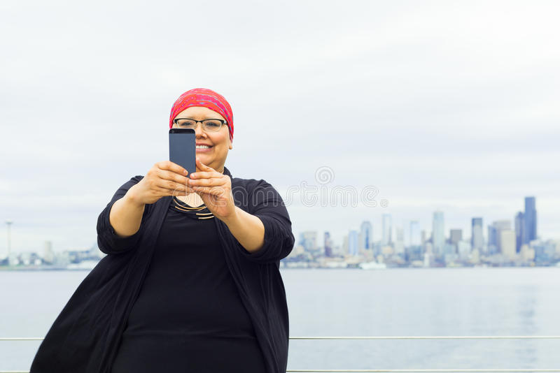 Woman Takes Selfie With Downtown Skyline In Background stock image