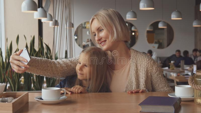Woman takes a selfie with her daughter at the cafe royalty free stock photos