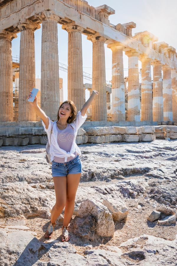 Woman takes selfie pictures in front of the Parthenon Temple at the Acropolis of Athens, Greece stock photography