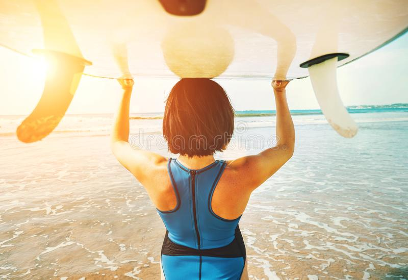 Woman takes surfboard on head and goes in ocean waves stock photos