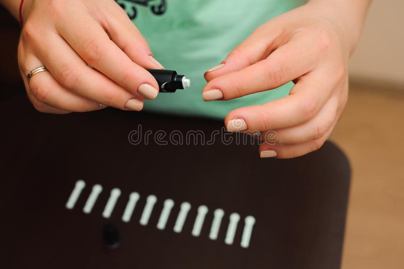Woman taking blood sample with lancet pen on wooden background. Diabetes concept royalty free stock photography