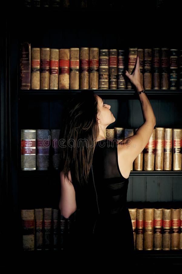 Woman taking a book from a bookstore. Woman sitting in an elegant bookstore with a black dress and light entering through the window royalty free stock image
