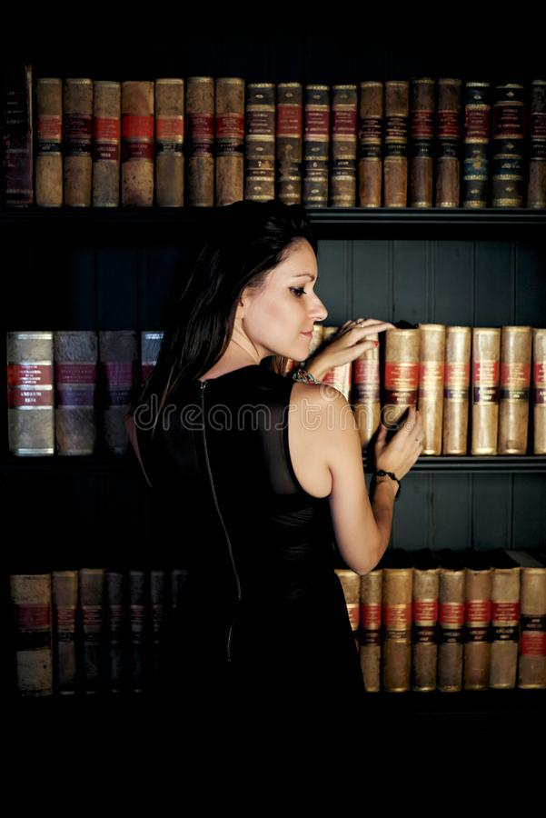Woman taking a book from a bookstore. Woman sitting in an elegant bookstore with a black dress and light entering through the window stock image